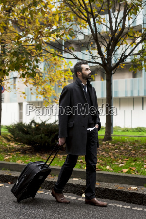 businessman with suitcase walking in the
