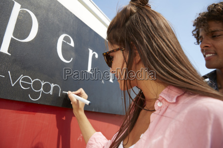 young woman writing the word vegan