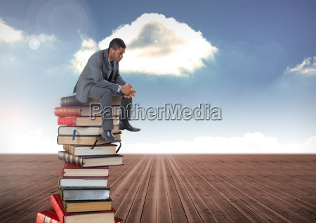 businessman sitting on books stacked by
