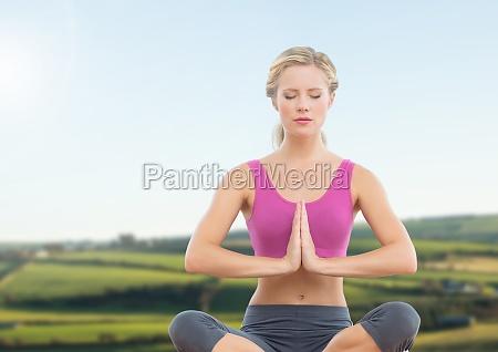 woman meditating by green fields
