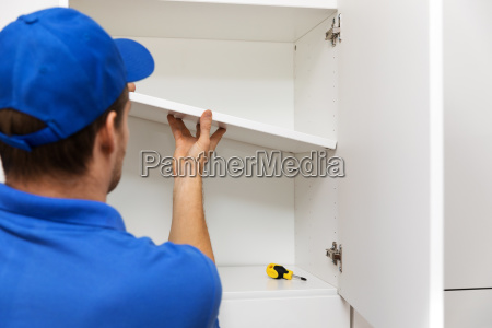 furniture assembly worker installing cabinet