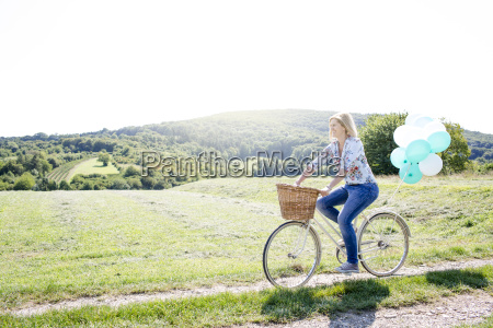 happy woman driving by bike with