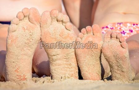 mutter und tochter fuesse mit strandsand