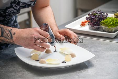 chef schmueckt vorspeise gericht