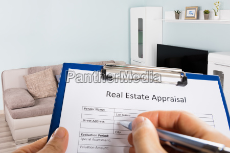 person hand filling real estate appraisal