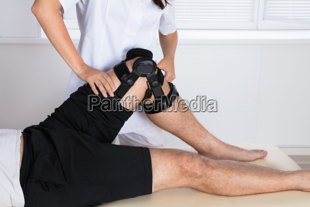 physiotherapeut der knie klammern auf dem