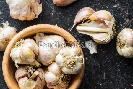 fresh healthy garlic in wooden bowl