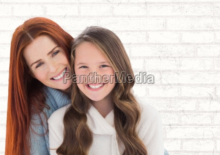 mother and daughter smilling against a