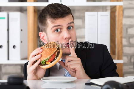 hungry young businessman holding burger with