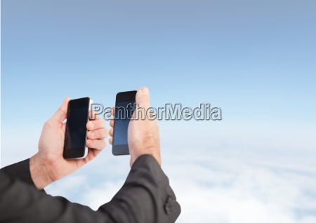hands holding two phones at same