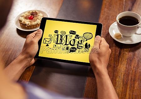 hands with tablet showing black blog