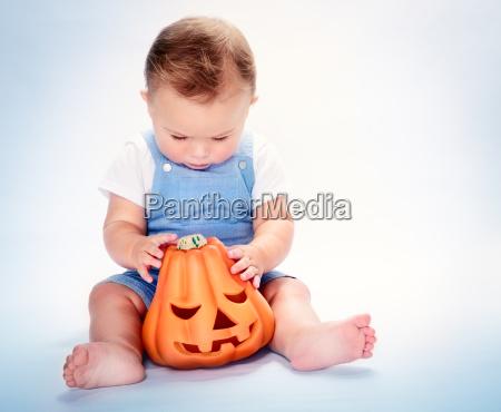 cute baby boy with halloween pumpkin