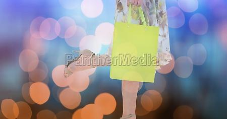 woman holding shopping bag over bokeh
