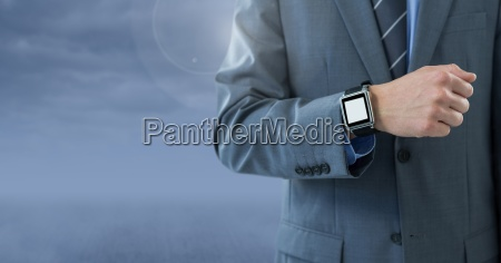 businessman with watch against blue cloudy