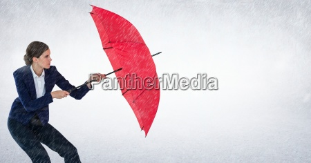 geschaeftsfrau mit regenschirm blockt regen vor