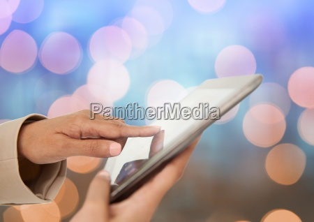 hand touching tablet with sparkling light