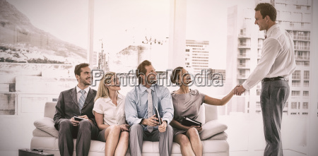 businessman shaking hand with woman sitting