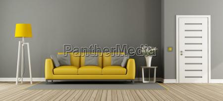 graues wohnzimmer mit gelbem sofa