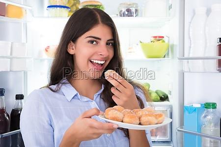 smiling woman eating cookies in plate