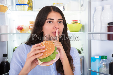 woman holding burger with finger on
