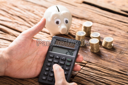 person calculating on calculator with coins