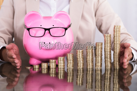businesswoman protecting stacked coins and piggy