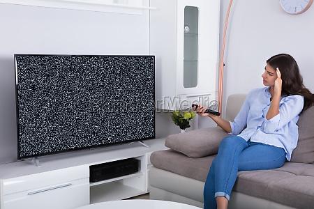 frau mit glitch fernseher frustriert