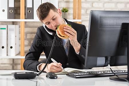 business man at desk eating burger