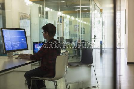 fokussierte jungenstudentenprogrammierung am computer im dunklen