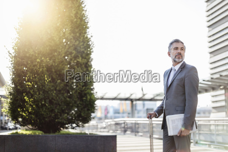 businessman with rolling suitcase outdoors