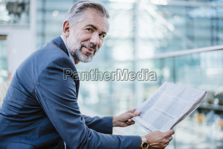 portrait of smiling businessman reading newspaper