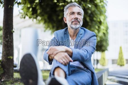 entspannter geschaeftsmann sitzt draussen an einer