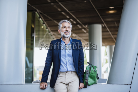 businessman at building with bag and