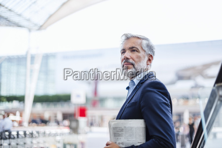 businessman outdoors holding newspaper