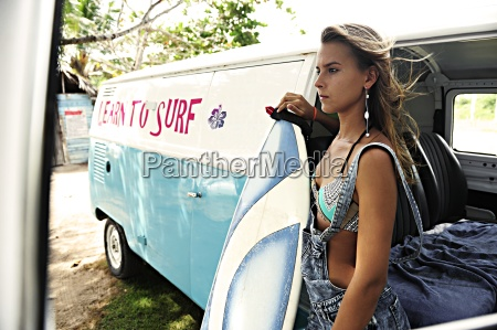 portrait of woman with surfboard at