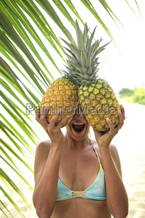 young woman holding two pineapples at