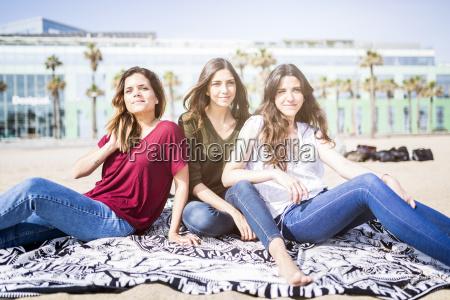 drei freundinnen am strand entspannen