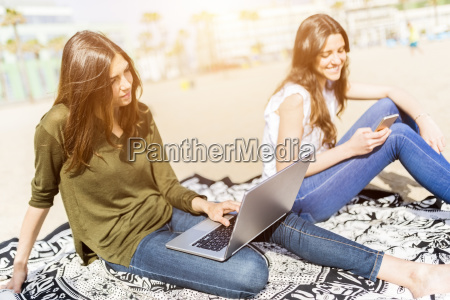 two young women using laptop and