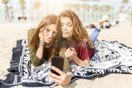 zwei verspielte freundinnen nehmen ein selfie