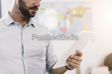 businessman using tablet partial view