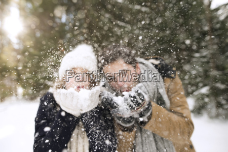 young couple blowing snow