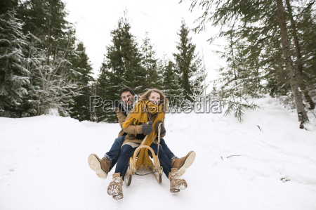 happy young couple on sledge in