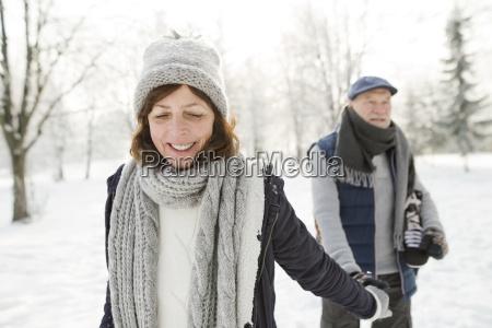 glueckliches seniorenpaar mit schlittschuhen zu fuss