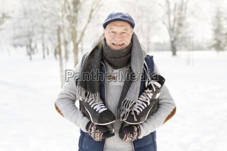 laechelnder senior mit schlittschuhen im winterwald