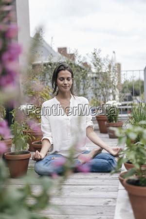 frau sitzt auf balkon und uebt