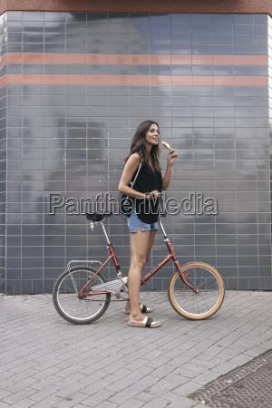 laechelnde frau mit eislutscher und fahrrad