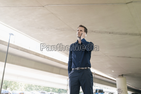 businessman on cell phone at underpass
