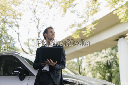 businessman standing next to car using