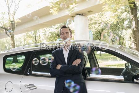 geschaeftsmann steht neben auto umgeben von