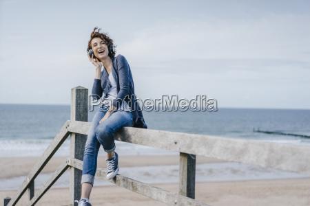 happy woman sitting on railing at